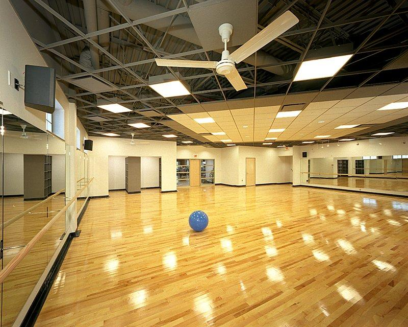Aerobics room with mirrors, a large fan and an exercise ball in the middle